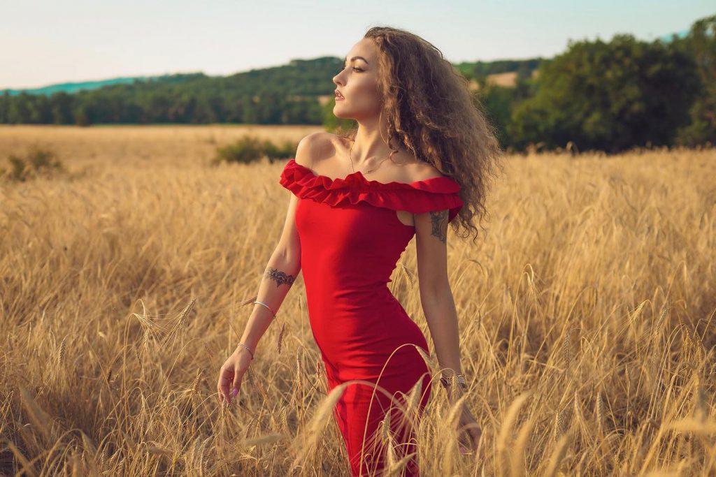Carlotta in abito rosso in un campo di grano a Pienza Val d'Orcia